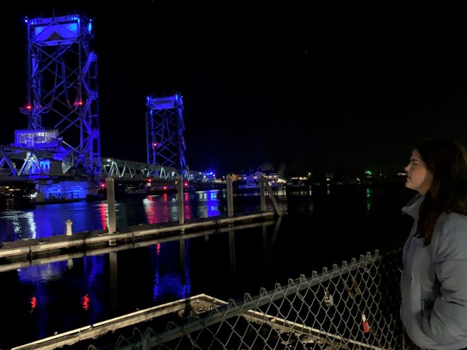 Elle Shaheen views the Memorial Bridge, one of many landmarks across the world lit up blue Saturday in recognition of World Diabetes Day, to raise awareness of a disease that strikes all populations and age groups. [Courtesy Photo]