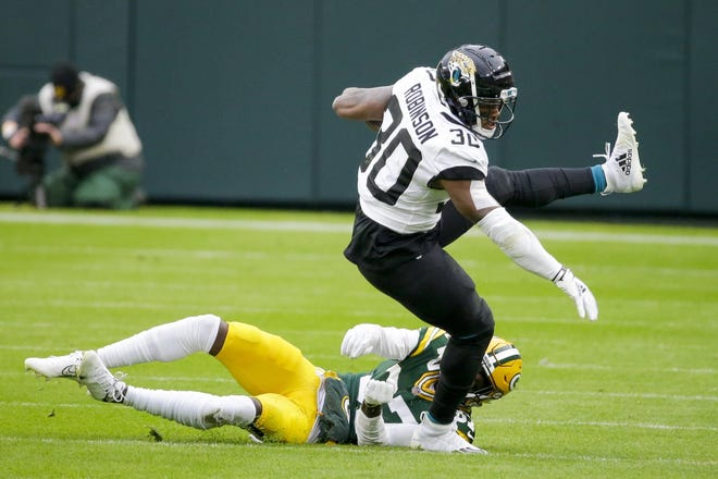 Jaguars running back James Robinson gets past Green Bay's Josh Jackson during the first half Sunday.