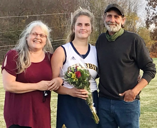 Quabbin senior Naomi Morrissey, center, celebrates Senior Day with her parents Holly and Peter Morrissey during a recent game in Barre. Naomi is the eighth member of her family to play field hockey for the Panthers.