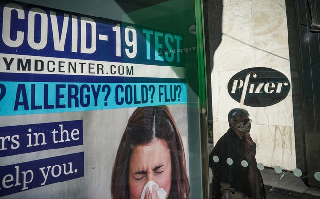A bus stop ad for COVID-19 testing is shown outside Pfizer world headquarters in New York on Monday. Pfizer said an early peek at its vaccine data suggests the shots may be 90% effective at preventing COVID-19, but it doesn't mean a vaccine is imminent.