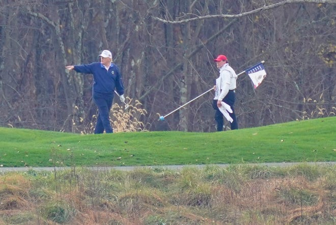 President Donald Trump, left, gesturing while playing golf at Trump National Golf Club in Sterling, Va., as seen from the other side of the Potomac River in Darnestown, Md., on Sunday.