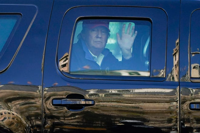 President Donald Trump waves to supporters from his motorcade as people gather for a march Saturday in Washington.