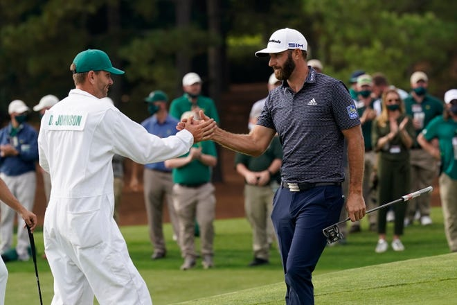 Dustin Johnson is congratulated by his caddie and brother, Austin Johnson, after winning the Masters golf tournament Sunday in Augusta, Ga.
