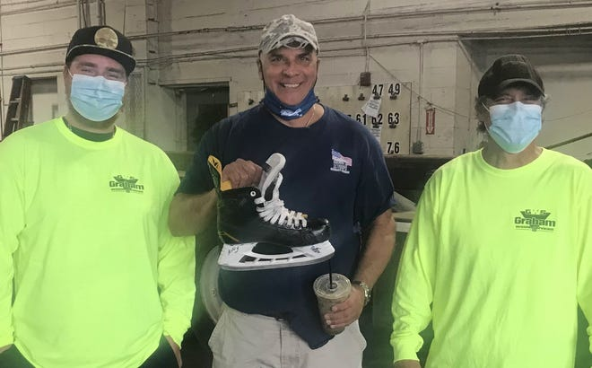 Mike Cogliano, center, with his ice skate, which was rescued by Peter Malone, left, and Andy Ramper, right, from a dumpster after it was thrown away following an apartment fire in Marshfield.