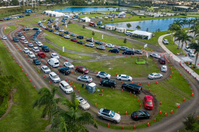 People line up in their cars to be tested for the coronavirus at the FitTeam Ballpark of the Palm Beaches in West Palm Beach on Saturday.