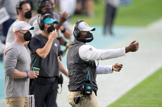 Coach Brian Flores gives instructions to the Dolphins against the Chargers on Sunday.