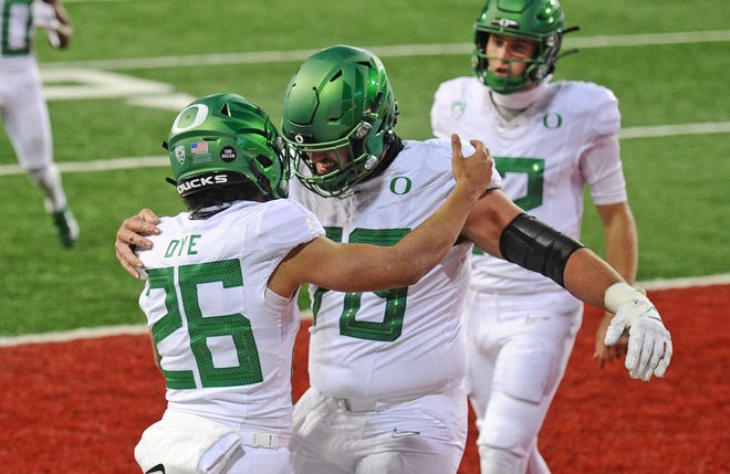Oregon running back Travis Dye (26) celebrates one of his two receiving touchdowns with center Alex Forsyth while quarterback Tyler Shough looks on during the Ducks' 43-29 win over Washington State.