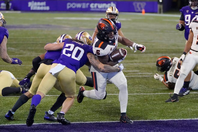 Oregon State's Jermar Jefferson runs past Washington's Asa Turner (20) for a first-half touchdown on Saturday in Seattle.
