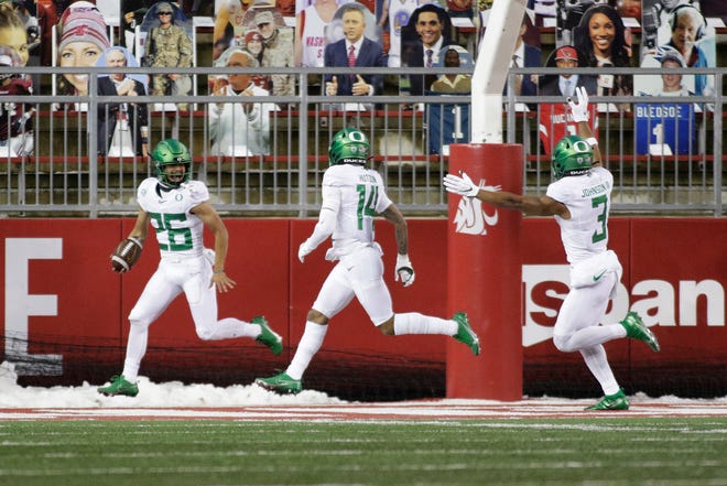 Oregon's Travis Dye (26) celebrates his 71-yard touchdown reception in the fourth quarter with wide receivers Kris Hutson (14) and Johnny Johnson III.