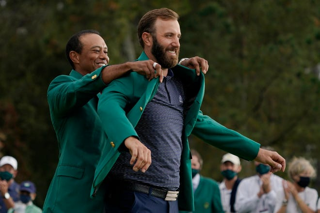 Tiger Woods helps Masters' champion Dustin Johnson with his green jacket after his victory at the Masters golf tournament on Sunday.