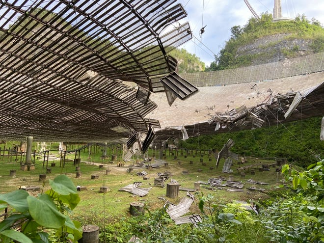 This August photo provided by the Arecibo Observatory shows the damage done by a broken cable that supported a metal platform, creating a 100-foot gash to the radio telescope's reflector dish in Arecibo, Puerto Rico.