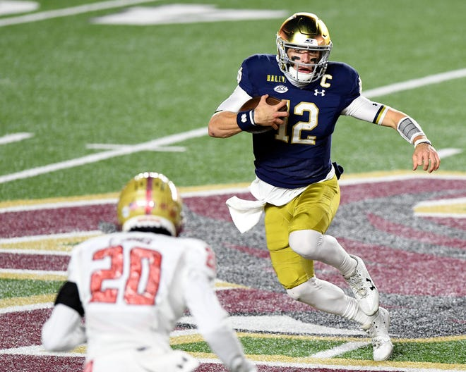 Notre Dame quarterback Ian Book runs with the ball against Boston College defensive back Elijah Jones during the first half.