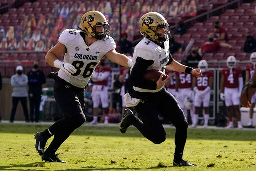 Colorado quarterback Sam Noyer, right, runs toward the end zone in front of tight end C.J. Schmanski to score a touchdown against Stanford during the first half on Saturday in Stanford, Calif. (AP Photo/Jeff Chiu)