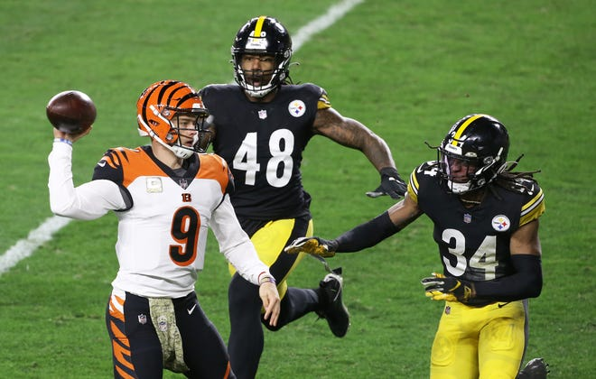 Nov 15, 2020; Pittsburgh, Pennsylvania, USA;  Cincinnati Bengals quarterback Joe Burrow (9) passes under pressure from Pittsburgh Steelers outside linebacker Bud Dupree (48) and strong safety Terrell Edmunds (34) during the second quarter at Heinz Field.