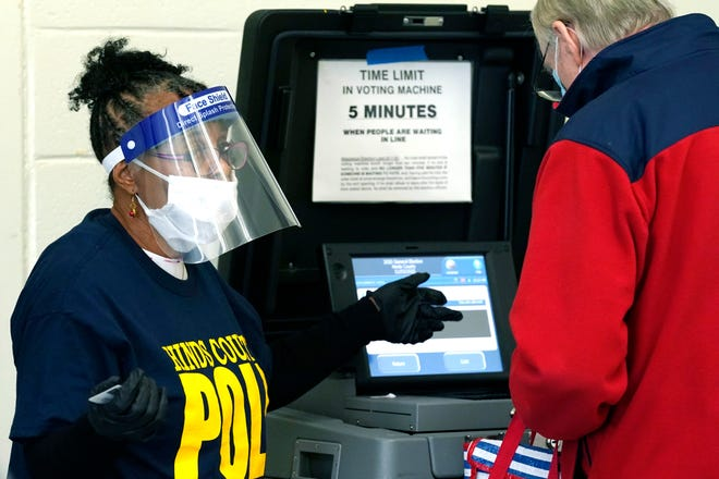 Poll worker Vivian Bibens wears personal protective equipment as she explains the workings of a ballot scanner to a voter on Election Day, Nov. 3, 2020, in Jackson, Miss.