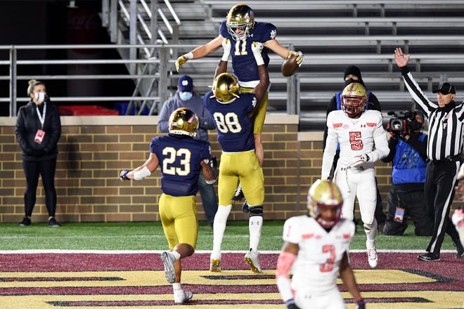 Notre Dame Fighting Irish wide receiver Ben Skowronek (11) is lifted by wide receiver Javon McKinley (88) after scoring a touchdown against the Boston College Eagles during the first half at Alumni Stadium.