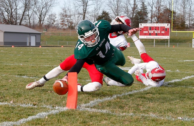 Portland St. Patrick's Connor Cross hits the pylon for a touchdown against Colon's Kaleb Johnson, right, and Ryan Bower, Saturday, Nov. 14, 2020, in Portland, Mich. St. Patrick won 44-34.