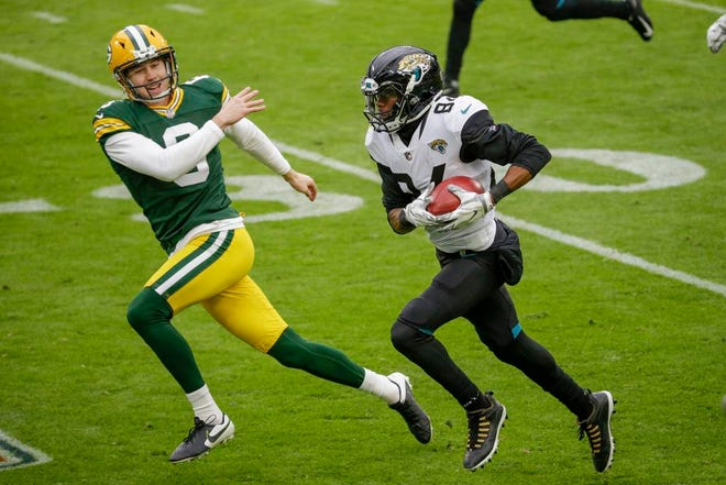 Green Bay Packers punter J.K. Scott can't stop Jacksonville Jaguars' Keelan Cole as he runs a punt back for a touchdown during the first half of an NFL football game Sunday, Nov. 15, 2020, in Green Bay, Wis.
