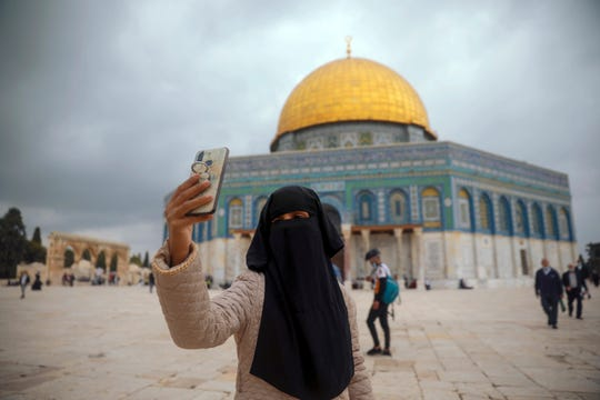 """A Muslim woman takes a photo next to the Dome of the Rock Mosque in the Al Aqsa Mosque compound in Jerusalem's old city, Friday, Nov. 6, 2020. The Palestinian leadership has condemned the United Arab Emirates' decision to forge ties with Israel as a """"betrayal,"""" but it could lead to a tourism bonanza for Palestinians in east Jerusalem as Israel courts wealthy Gulf travelers."""