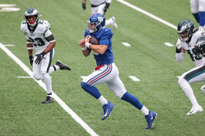 New York Giants quarterback Daniel Jones (8) rushes for a touchdown as Philadelphia Eagles safety Rodney McLeod (23) pursues  during the first half at MetLife Stadium.