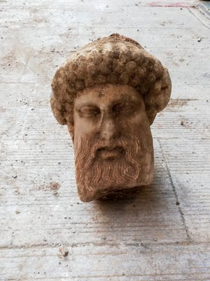 """In this undated photo, provided by the Greek Culture Ministry on Sunday, Nov. 15, 2020, a head of the ancient god Hermes is pictured after being found during sewage works in central Athens. The ministry said Sunday that the head, depicting Hermes at a """"mature age"""", one of many that served as street markers in ancient Athens, appears to be from around 300 BC, that is, either from the late 4th century BC, or the early 3rd century."""