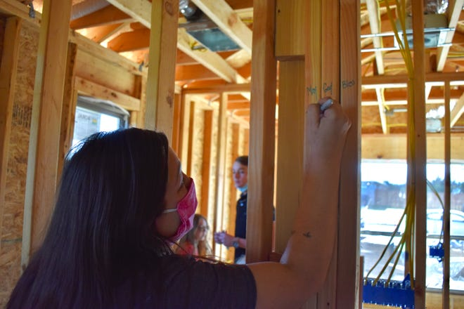 Dee O'Hare's oldest daughter, Amanda, signs a beam in the family's new house during a blessing ceremony on Monday, Nov. 16.
