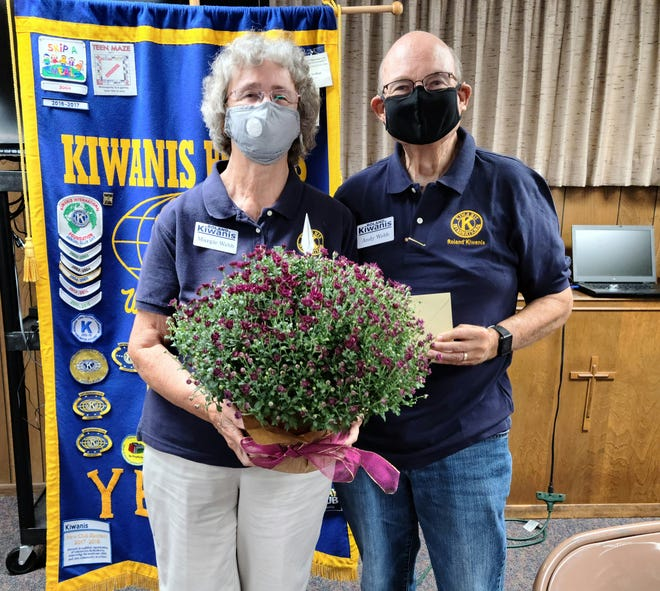 """Margie Webb, outgoing president of Roland Kiwanis, received flowers and """"thanks"""" from incoming president,  Andy Webb, who is also Roland's mayor."""
