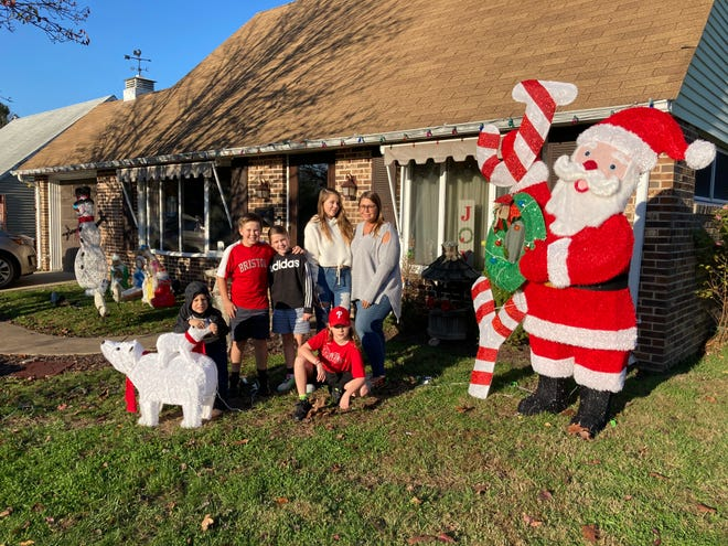 """Lindsay Fantini (right in glasses) poses with her children and several neighborhood kids in front of her house on Cobalt Ridge Drive North in Levittown. """"It's the first time I've been this early with them, and I know people will say it's kind of crazy but, as I told the kids, 2020 has been kind of crazy,"""" she said."""