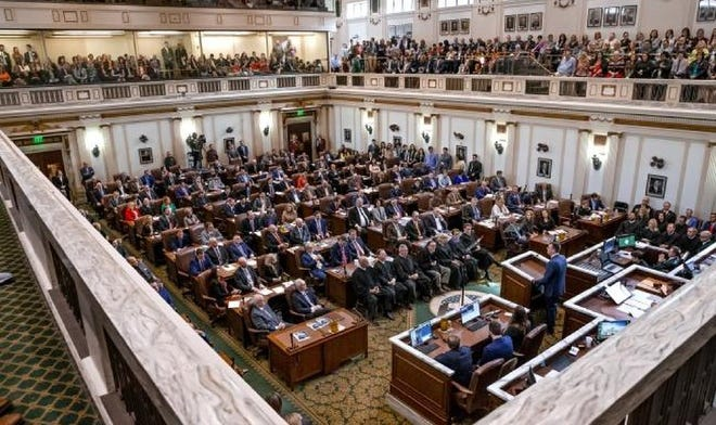 Annual pay for Oklahoma's lawmakers will go up 35% this week, for the first increase in more than two decades. Here, legislators gather in the House of Representatives on Feb. 3 as Gov. Kevin Stitt delivers his State of the State Address.