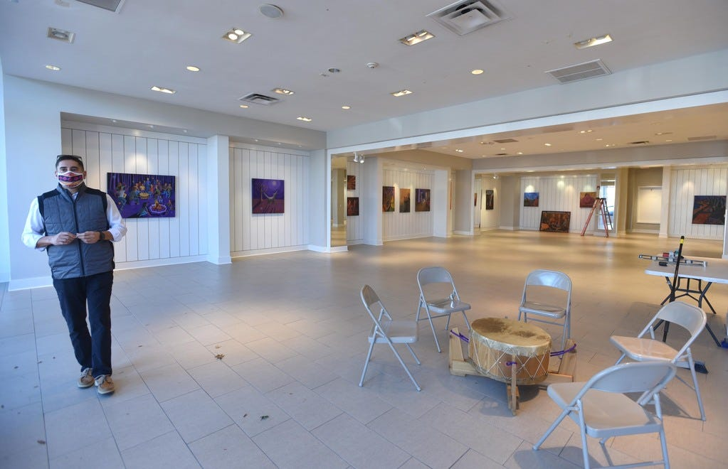 Steven Peters, a spokesman for the Mashpee Wampanoag Tribe, stands in a gallery opened for Native American Heritage Month. The Wampanoag Trading Post and Gallery is featuring an exhibit of artwork and movies by and about the tribe at its Mashpee Commons location and at a vacant storefront across the street.