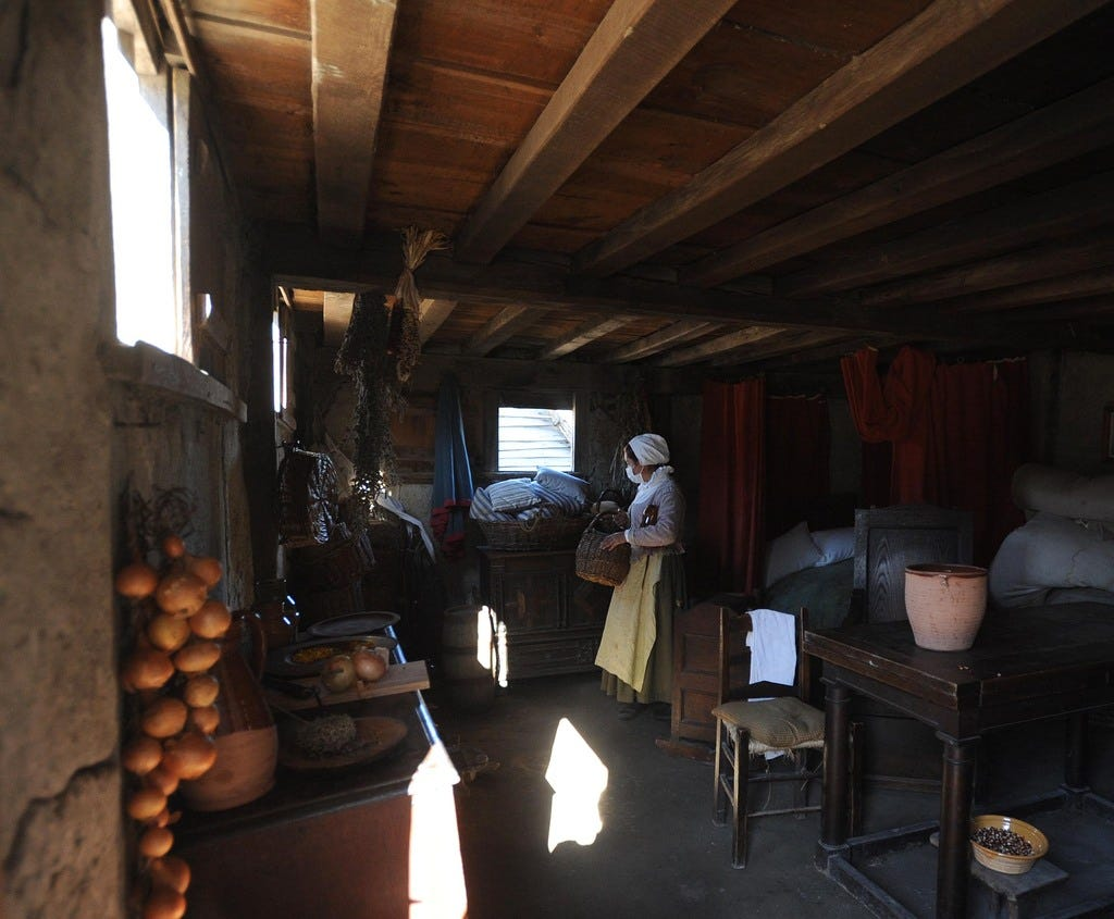 An interpreter, wearing a mask because of the COVID-19 pandemic, works in a replica of a period house at the Pilgrim Village at Plimoth Patuxet living history museum.
