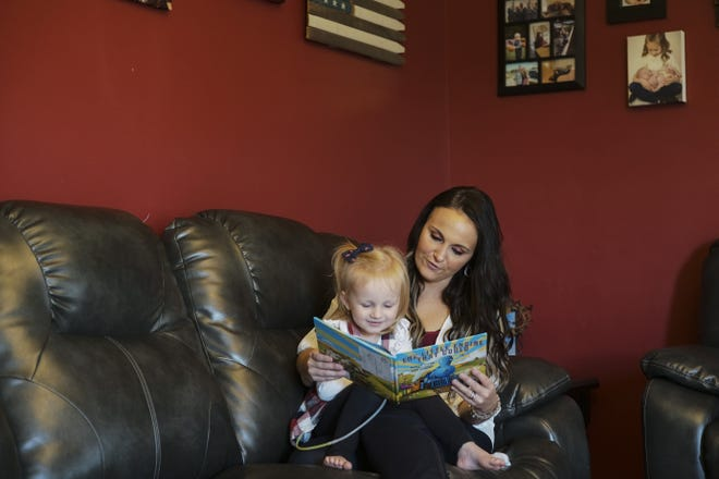 """Haley Allgood and her daughter, Novalee, 2, read """"The Little Engine that Could"""" at their home in Leesburg, in Highland County. Books received through Dolly Parton's Imagination Library have helped her and others in rural Ohio, where access to libraries is difficult."""