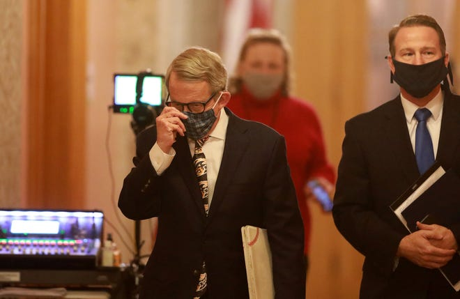 Ohio Gov. Mike DeWine (left) and Lt. Gov. Jon Husted wear their masks while walking to a coronavirus news conference in April at the Ohio Statehouse. (Doral Chenoweth/Columbus Dispatch)