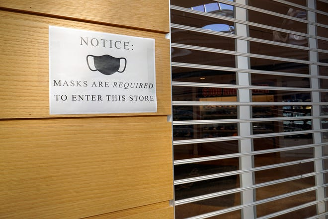 A notice to customers about wearing masks is posted on a wall at the Mall at Tuttle Crossing in Dublin.