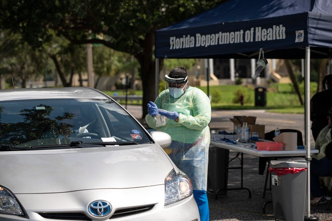 A health care worker administers a test for COVID-19 at Lake-Sumter State College in Leesburg. [Cindy Peterson/Correspondent]