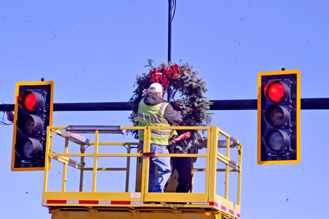 City of Wooster employees Gerry Martin and George Grande placed 18 large holiday wreathes at downtown intersections just in time for Window Wonderland, which kicked off the holiday season in the city on Friday. Festivities continue throughout the remainder of November and December.