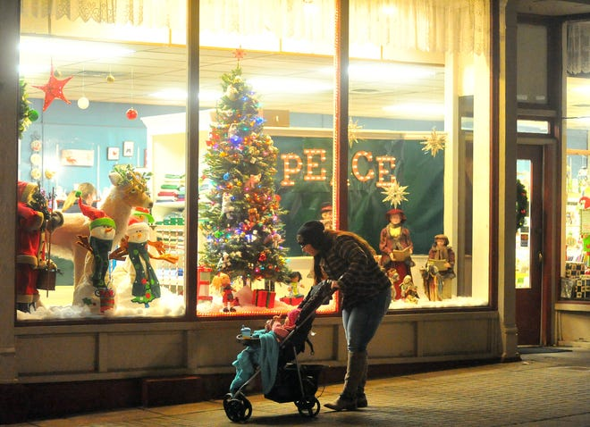 A mother and her child look at the window display outside the Gift Corner during Window Wonderland last year. Window Wonderland will be held in downtown Wooster on Friday. Children can have a photo taken with Santa, who will be behind a window, from 3-8 p.m.
