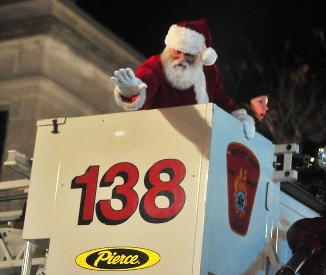 Santa waves to everyone below him as he's lowered to the ground by a Wooster Fire Department truck during Window Wonderland in 2019.