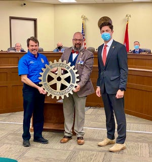 """A """"rotary wheel"""" monument is donated to Mayor Chaz Molder, right, and Columbia City Council by Columbia Noon Rotary president Mark Mayberry, left, and past president Eric Previti, center. The monument will be placed on the sidewalk on West 7th Street in front of the Memorial Building."""