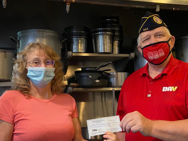 Mike Slish, right, presents a $250 check to Laura Dyser.