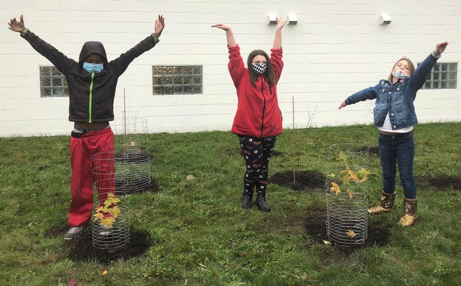 From left: Students Espoir Niringiyimana, 10; Kylie Rose Hadden, 10; and Tempie Cioccio, 9, celebrate after planting trees at the Inner-City Neighborhood Art House, 201 E. 10th St., as part of a ReLeaf project.