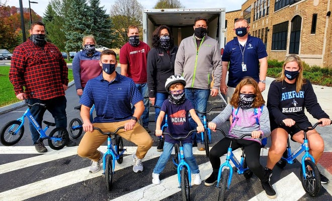 Ready to pedal, front row from left, Reed Warner, physical education teacher; Max Marcus, first grade student; Maddie Marcus, fourth grade student; Kate Crowell, physical education teacher. Back row from left, Michael Studley, Abbey Keogan and Ryan Hurlburt, Maddies Motor Sports' staff members; Mary Marcus and Graham Marcus, owners of Maddies Motor Sports; Daniel Paulus, physical education teacher.