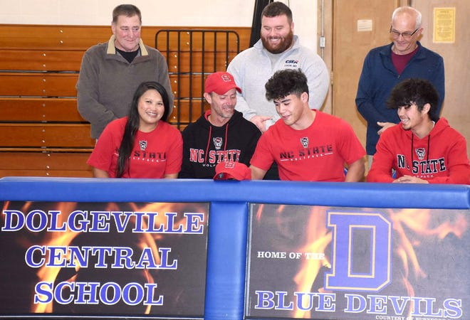 Dolgeville senior Jake Null signs his National Letter of Intent to attend and wrestle at North Carolina State University Friday in a school gymnasium. Pictured above (from left) are: Front – Null's parents, Daisy and Ryan Null, Jake Null and his brother, Anthony Chromczak; and Back – coaches John Treen, Kasey Foster and David Haughton.