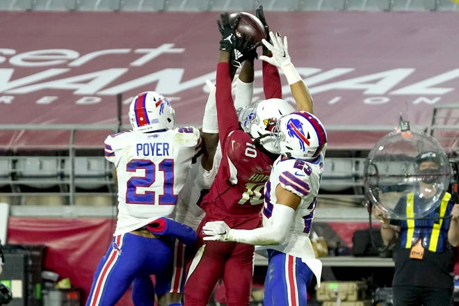 Arizona Cardinals wide receiver DeAndre Hopkins pulls in the game-winning touchdown pass as Buffalo Bills free safety Jordan Poyer (21) and strong safety Micah Hyde defend during at the end of Sunday's game in Glendale, Arizona. The Cardinals won 32-30.