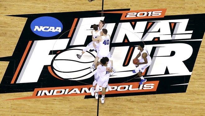 Duke players celebrate after beating Wisconsin in the NCAA basketball tournament championship game in Indianapolis April 6, 2015. The NCAA announced Monday it plans to hold the entire 2021 men's college basketball tournament in one geographic location to mitigate the risks of COVID-19 and is in talks with Indianapolis to be the host city