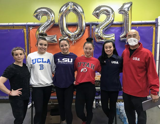 Flanked by Great American Gymnastics Express (GAGE) coach Armine Barutyan, left, and her husband, Al Fong, right, are GAGE gymnasts, from left, Alexis Jeffrey, Aleah Finnegan, Kara Eaker and Leanne Wong, who signed their national letters of intent to continue their gymnastic careers at Division I universities across the country.