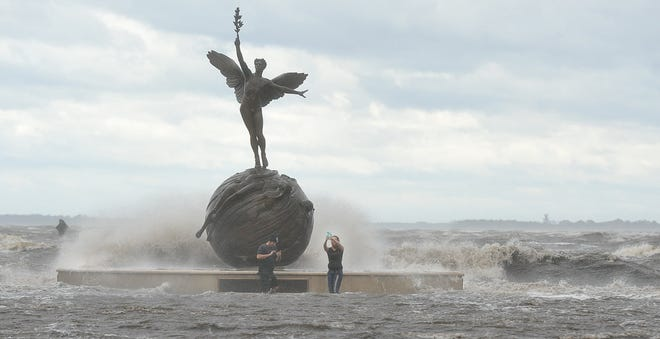 """During Hurricane Irma residents take selfies at the """"Life"""" statue in Memorial Park as waves from the St. Johns River break over the bulkhead and railing on Sept. 11, 2017, in Jacksonville."""