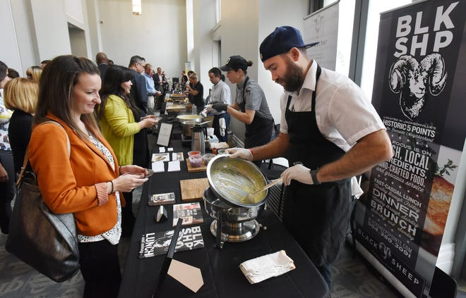 Waylon Rivers, executive chef at Black Sheep serves up the final bowl of his broccoli and cheddar cheese soup to Stella Varkanis during the 2018 Empty Bowls luncheon benefiting Feeding Northeast Florida. This year the fundraiser will be virtual.