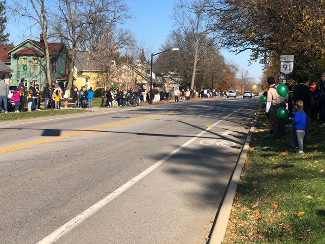 Residents line up along Main Street in Hudson for the funeral procession of Vincent Baran on Saturday.