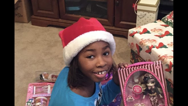 Courtney Jones holds up a gift during Christmas. She died from complications due to leukemia in April 2018.
